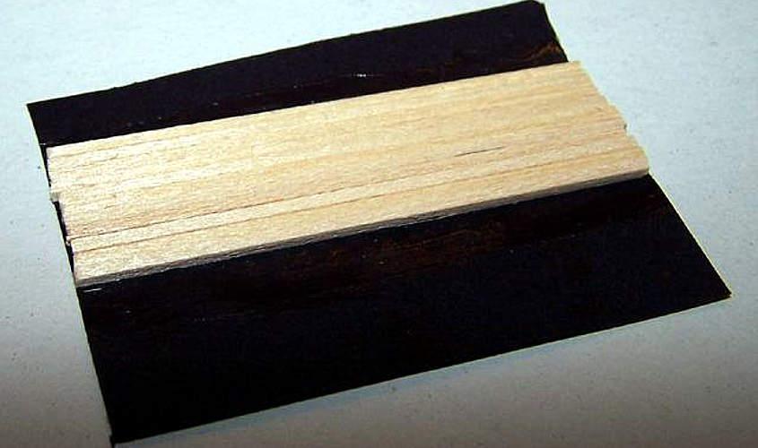 Su un foglio di carta nera si incollano dei listelli di tiglio