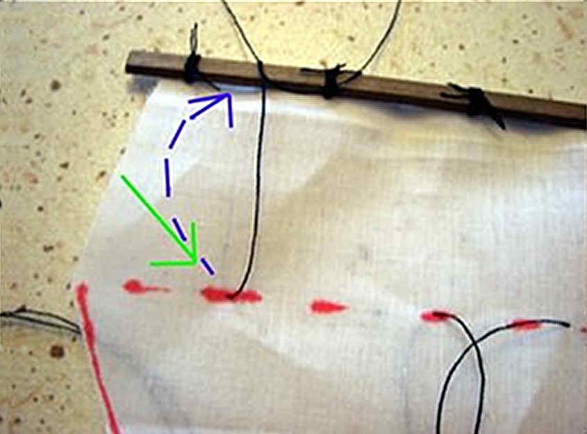 Si passano i fili da dietro la vela e sopra al pennone