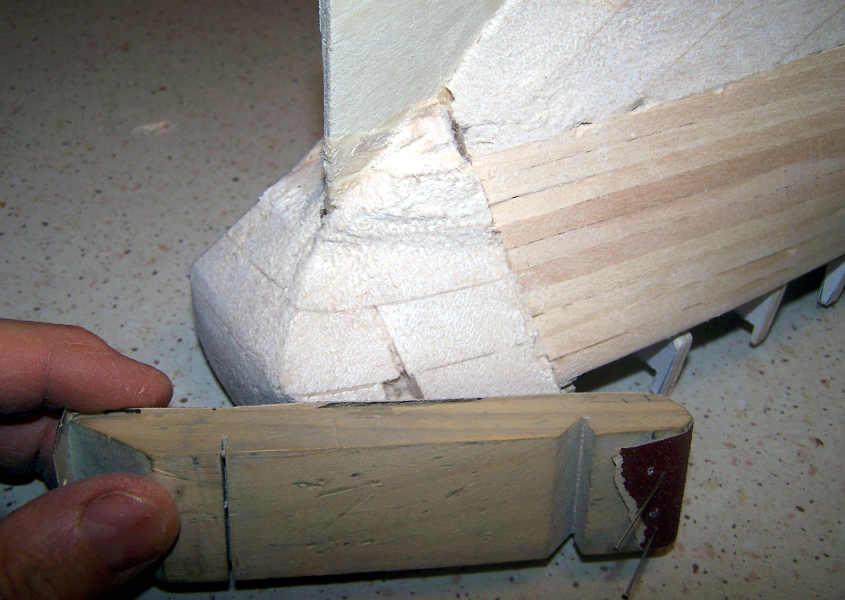 Utilizzando sempre un lisciatoio pareggio la poppa alla sagoma dello scafo.