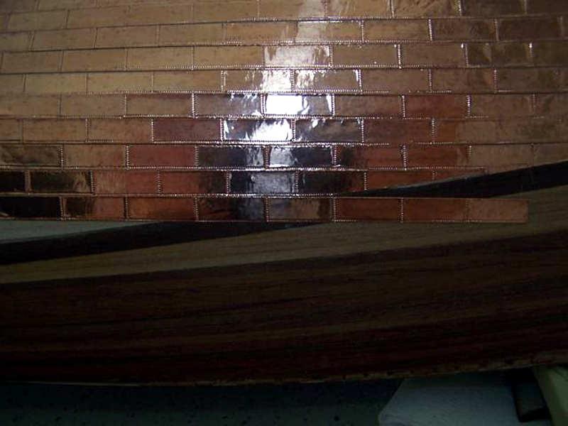 Anche verso il centro dello scafo si deve procedere ad eliminare l'eccesso del rivestimento.